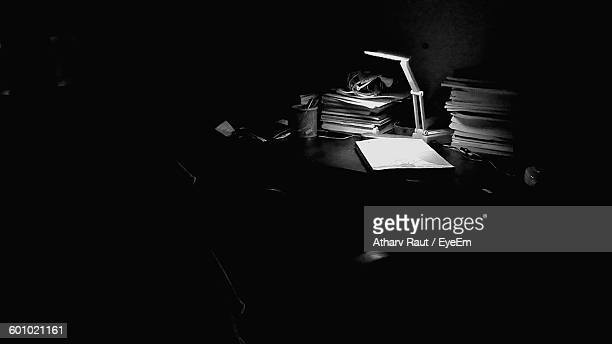 High Angle View Of Electric Lamp With Documents On Table