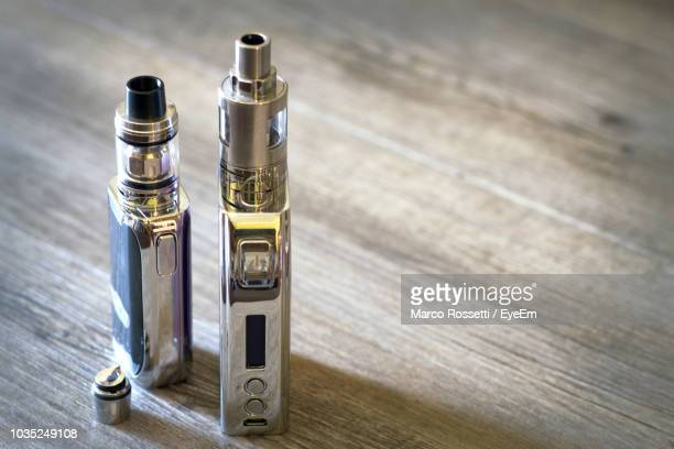 high angle view of electronic cigarette on wooden table - vaping stock photos and pictures