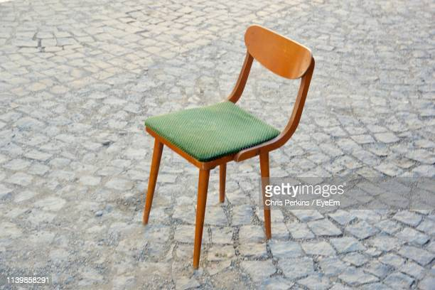 High Angle View Of Empty Chair On Footpath