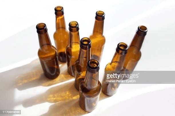 high angle view of empty glass bottles on table at home - beer bottle stock pictures, royalty-free photos & images