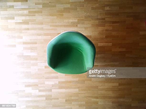 High Angle View Of Empty Green Chair On Hardwood Floor