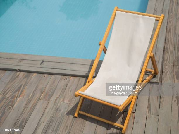 high angle view of empty lounge chair against swimming pool - chaise longue photos et images de collection