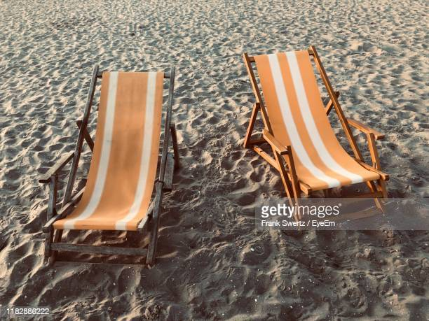 high angle view of empty lounge chairs at beach - frank swertz stockfoto's en -beelden