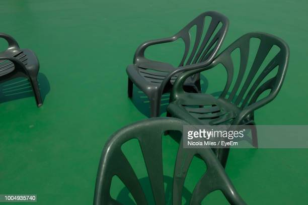 High Angle View Of Empty Plastic Chairs On Green Floor