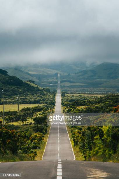 high angle view of empty road leading towards mountains against sky - thoroughfare stock pictures, royalty-free photos & images
