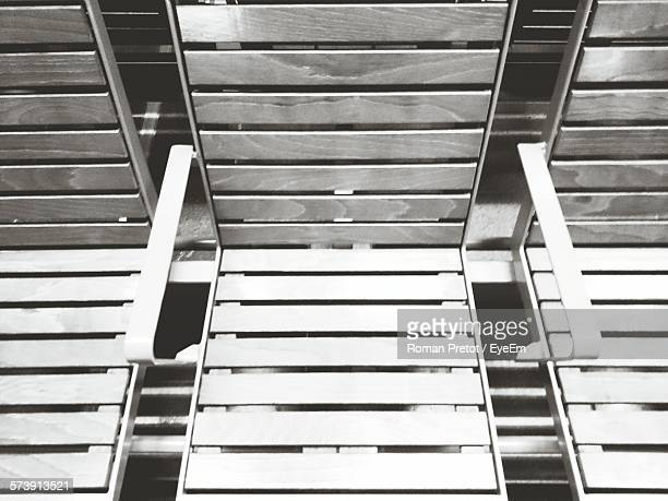high angle view of empty wooden seats at railroad station platform - roman pretot stock-fotos und bilder