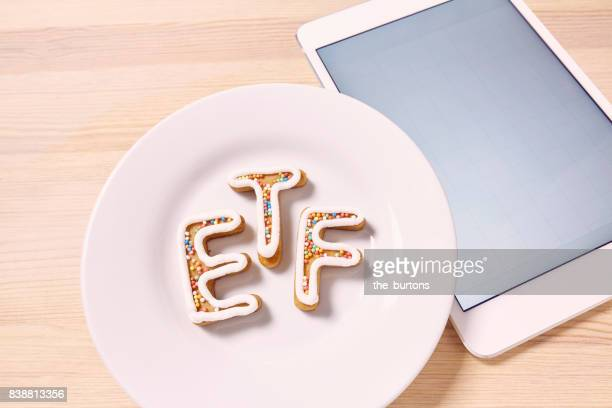 High angle view of ETF letters on plate (symbol of investment in stocks) with tablet computer
