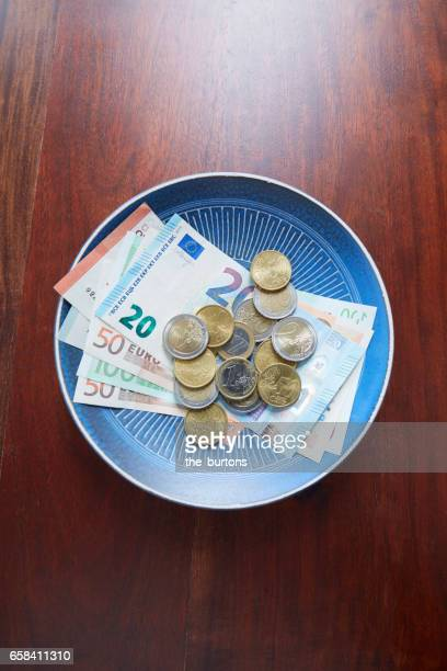 High angle view of Euro notes and coins on plate