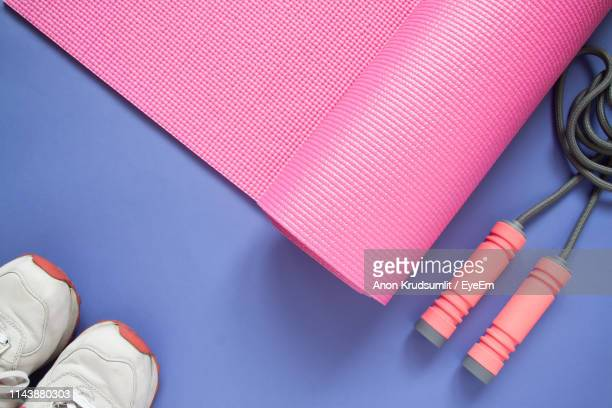 high angle view of exercise mat and shoes on purple background - mat stock pictures, royalty-free photos & images