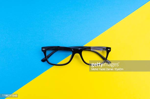 high angle view of eyeglasses against two tone background - bicolore photos et images de collection