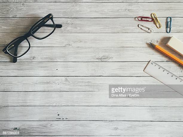 High Angle View Of Eyeglasses And Office Supply On Table