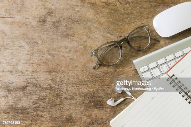 high angle view of eyeglasses and office supply on wooden table - office desk top view stock photos and pictures