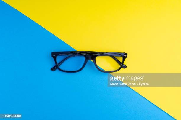 high angle view of eyeglasses over colored background - ツートンカラー ストックフォトと画像