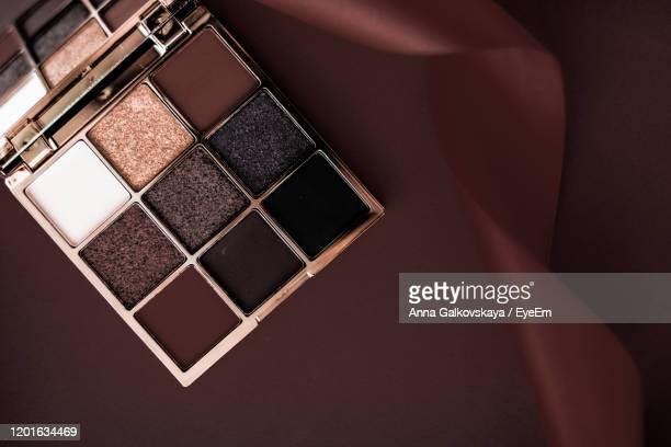 high angle view of eyeshadow on brown background - アイシャドウ ストックフォトと画像