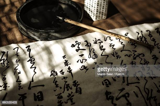 High Angle View Of Fabric With Calligraphy Brush On Table