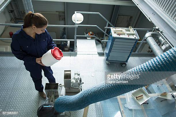 high angle view of factory worker reading instructions on plastic container - sigrid gombert stock-fotos und bilder