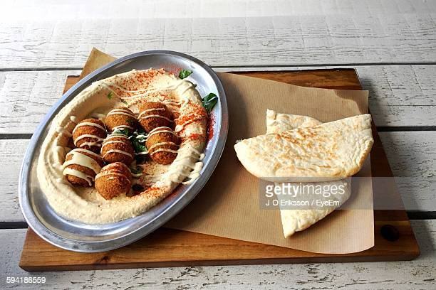High Angle View Of Falafel, Hummus And Pita Bread Served On Cutting Board