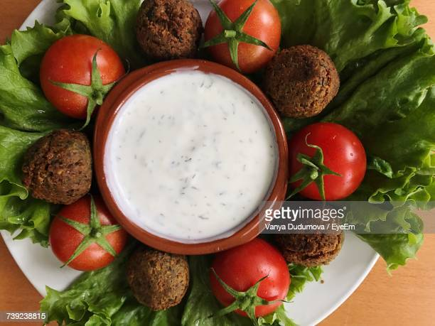High Angle View Of Falafels With Cherry Tomatoes And Dip In Plate On Table