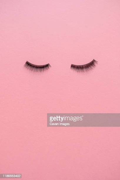 high angle view of false eyelashes on pink table - false eyelash stock pictures, royalty-free photos & images