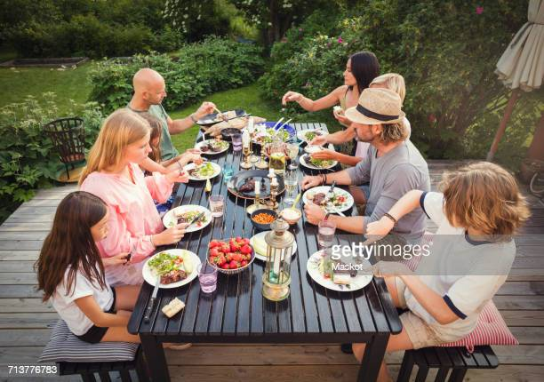 high angle view of family and friends eating lunch in back yard - family lunch fotografías e imágenes de stock