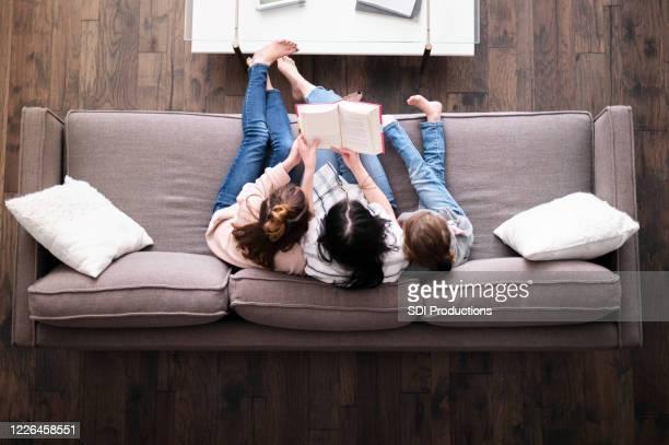 hög vinkel syn på familjen läsning tillsammans - bibel bildbanksfoton och bilder
