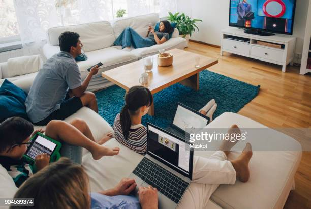 high angle view of family using technologies while relaxing in living room at home - televisión fotografías e imágenes de stock