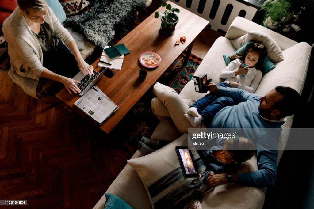 High angle view of family using various technologies in living room at home : Stock Photo