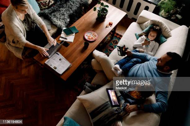 high angle view of family using various technologies in living room at home - apparatuur stockfoto's en -beelden