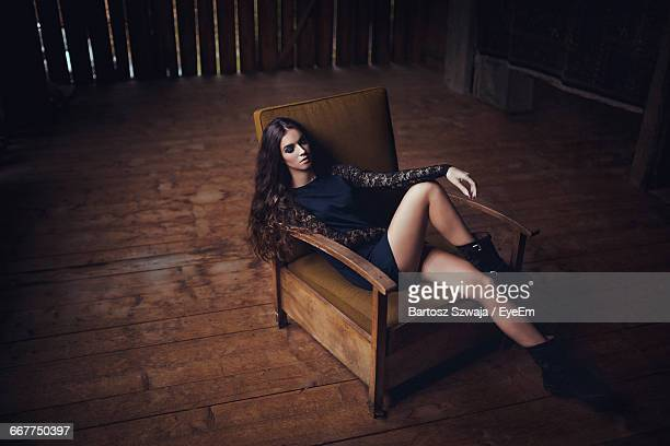 High Angle View Of Fashion Model Sitting On Chair In Room