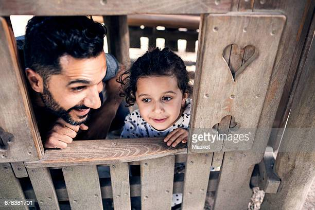 High angle view of father and daughter playing in wooden toy house