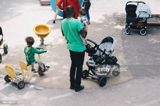 High angle view of father carrying toddler while standing by son riding tricycle at park