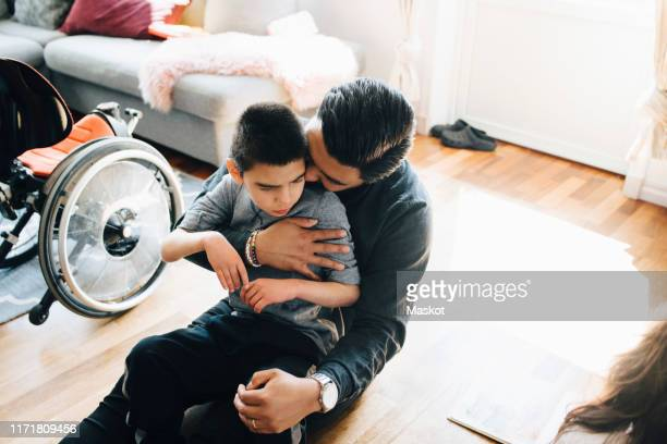 high angle view of father holding autistic son while sitting on floor at home - differing abilities fotografías e imágenes de stock