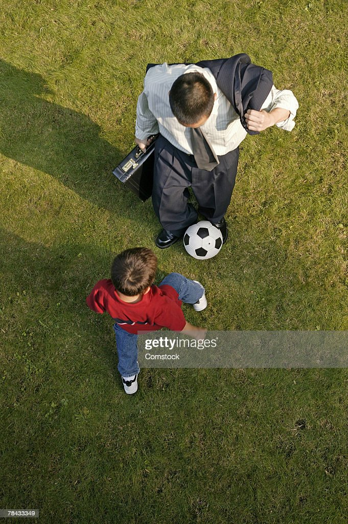 High angle view of father kicking soccer ball with son : Stockfoto