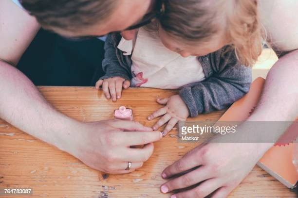High angle view of father painting daughters nails at table outdoors