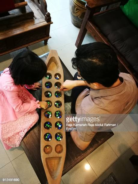 high angle view of father playing with daughter at home - terengganu stock pictures, royalty-free photos & images