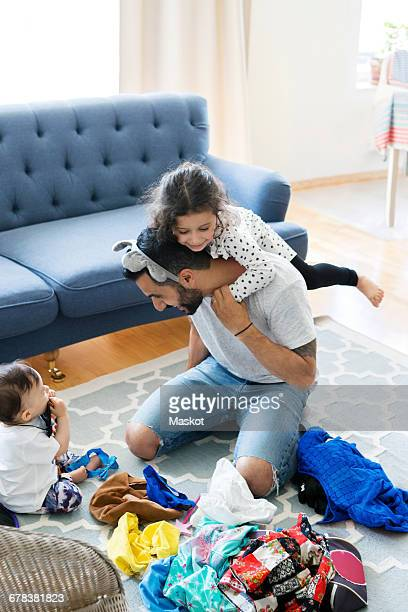 High angle view of father playing with daughters on carpet at home