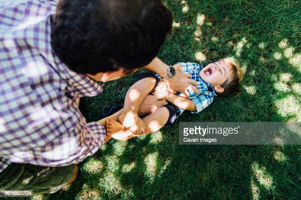 high angle view of father playing with son on grassy field - tickling stock pictures, royalty-free photos & images