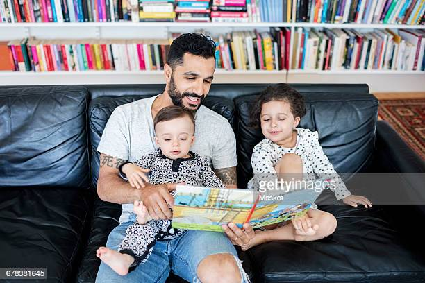 High angle view of father reading book to children while sitting on sofa at home