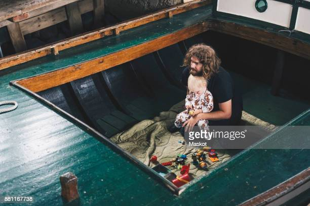 High angle view of father sitting with toddler in boat