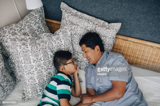High angle view of father talking to son while lying on bed at home