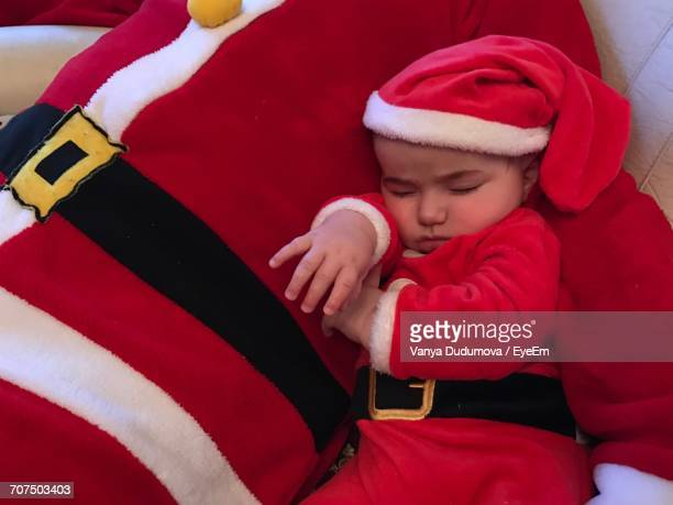 High Angle View Of Father With Baby In Santa Claus Costume At Home
