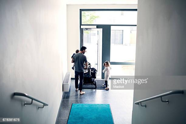 High angle view of father with children holding baby stroller while standing in corridor