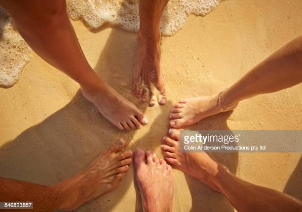 High angle view of feet of friends on beach