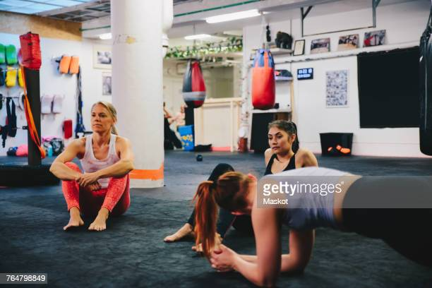 High angle view of female athletes resting on floor at health club