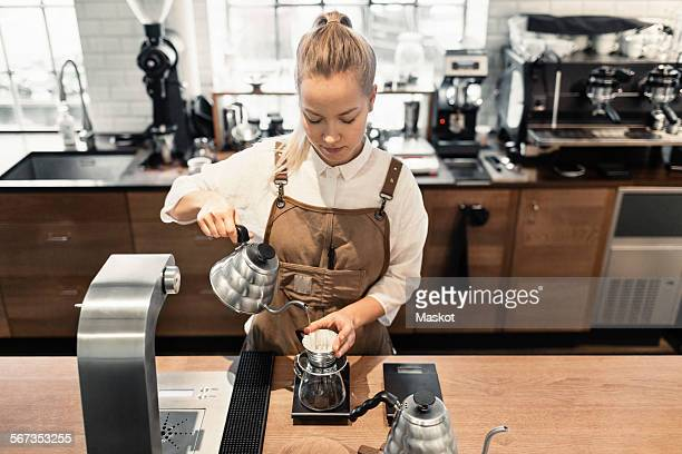 High angle view of female barista pouring boiling water in coffee filter at cafe counter