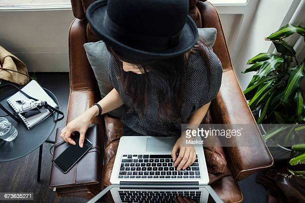 High angle view of female blogger using phone and laptop while sitting on chair