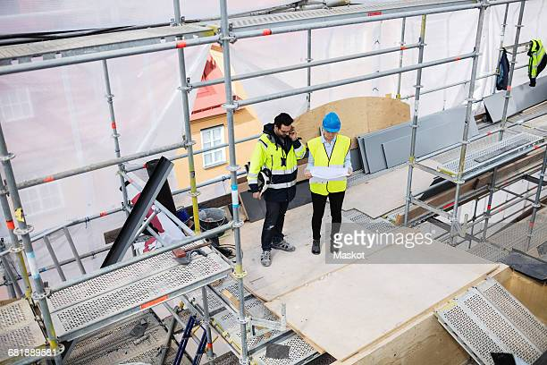 High angle view of female coworker reading documents while manager talking on phone at construction site