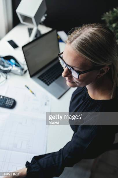 high angle view of female engineer with blueprint and laptop on desk - 女性建築家 ストックフォトと画像