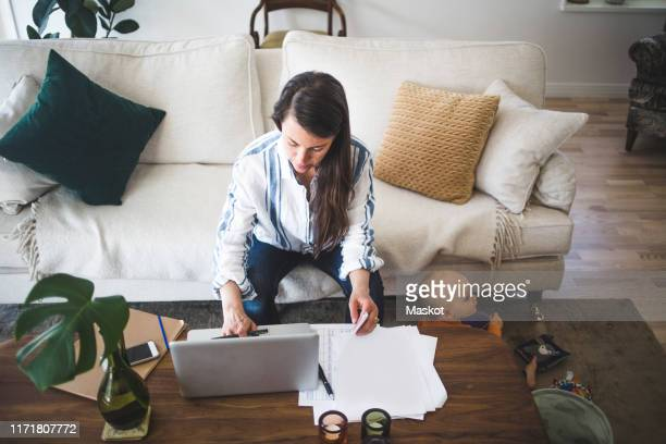 high angle view of female entrepreneur concentrating on work while daughter playing at home office - working from home stock pictures, royalty-free photos & images