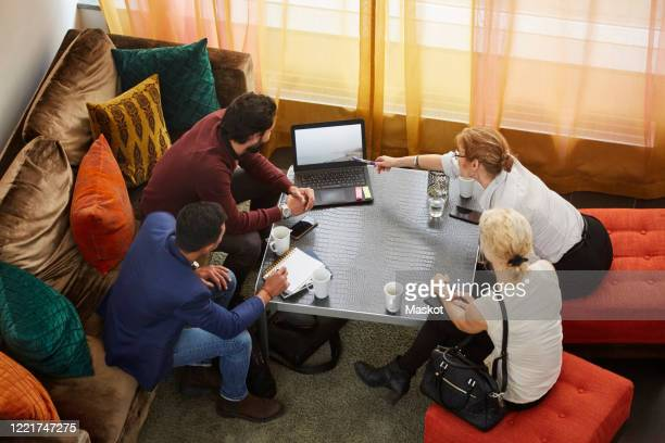 high angle view of female entrepreneur discussing with colleagues while sitting by table in office seminar - representative member of congress stock pictures, royalty-free photos & images